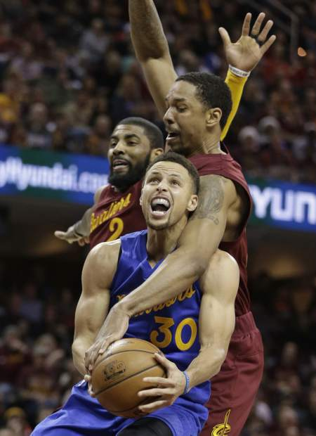 From foreground, Golden State Warriors' Stephen Curry is fouled by Cleveland Cavaliers' Channing Frye as Kyrie Irving defends in the second half of an NBA basketball game, Sunday, Dec. 25, 2016, in Cleveland. The Cavaliers won 109-108. (AP Photo/Tony Dejak)