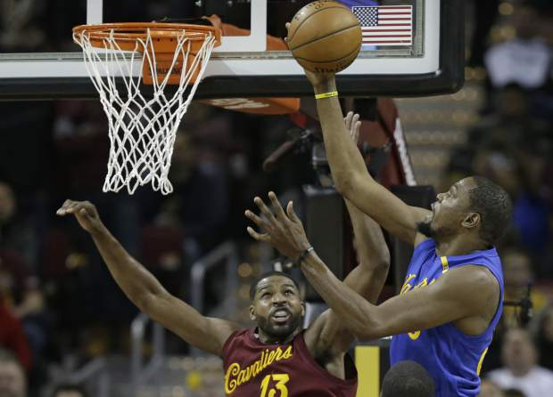 Golden State Warriors' Kevin Durant, right, drives to the basket against Cleveland Cavaliers' Tristan Thompson in the first half of an NBA basketball game, Sunday, Dec. 25, 2016, in Cleveland. (AP Photo/Tony Dejak)