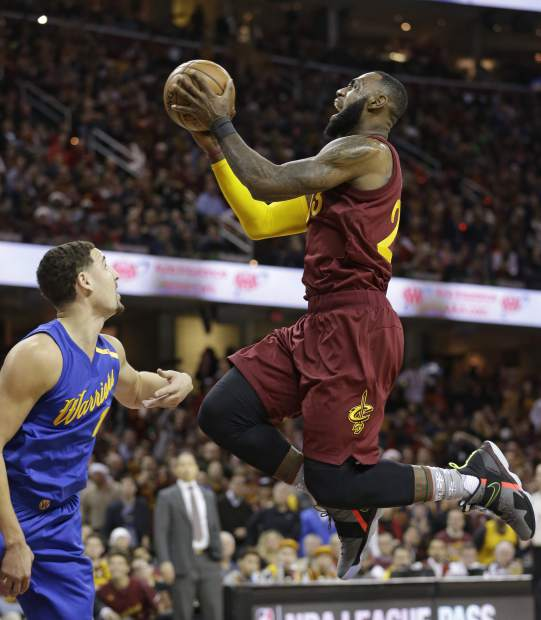 Cleveland Cavaliers' LeBron James, right, drives to the basket against Golden State Warriors' Klay Thompson in the first half of an NBA basketball game, Sunday, Dec. 25, 2016, in Cleveland. (AP Photo/Tony Dejak)
