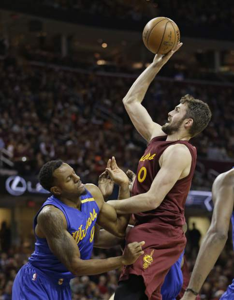 Golden State Warriors' Andre Iguodala, left, fouls Cleveland Cavaliers' Kevin Love in the first half of an NBA basketball game, Sunday, Dec. 25, 2016, in Cleveland. (AP Photo/Tony Dejak)