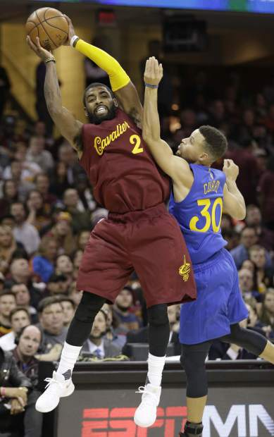 Cleveland Cavaliers' Kyrie Irving (2) passes over Golden State Warriors' Stephen Curry (30) in the first half of an NBA basketball game, Sunday, Dec. 25, 2016, in Cleveland. (AP Photo/Tony Dejak)