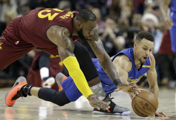 Cleveland Cavaliers' LeBron James, left, and Golden State Warriors' Stephen Curry battle for a loose ball in the second half of an NBA basketball game, Sunday, Dec. 25, 2016, in Cleveland. The Cavaliers won 109-108. (AP Photo/Tony Dejak)