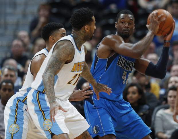 Dallas Mavericks forward Harrison Barnes, right, looks to pass the ball as Denver Nuggets forward Wilson Chandler, front left, and guard Gary Harris defend in the second half of an NBA basketball game, Monday, Feb. 6, 2017, in Denver. The Nuggets won 110-87. (AP Photo/David Zalubowski)