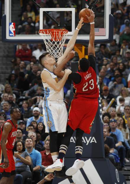 New Orleans Pelicans forward Anthony Davis, right, goes up for a dunk as Denver Nuggets forward Juan Hernangomez defends during the second half of an NBA basketball game Sunday, March 26, 2017, in Denver. The Pelicans won 115-90. (AP Photo/David Zalubowski))
