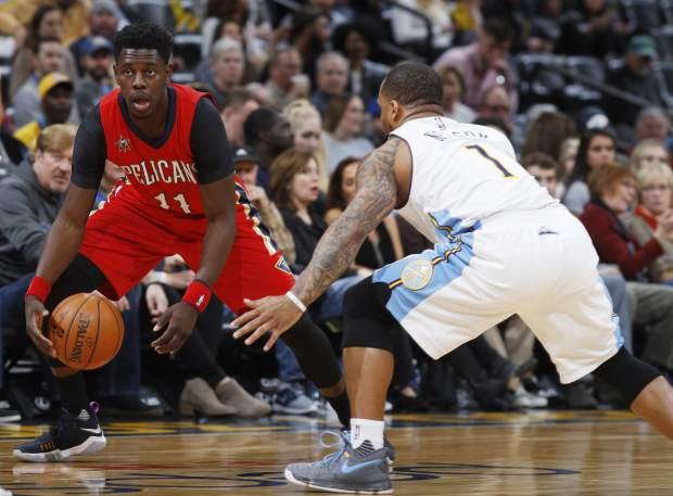New Orleans Pelicans guard Jrue Holiday, left, picks up a loose ball as Denver Nuggets guard Jameer Nelson defends during the first half of an NBA basketball game Sunday, March 26, 2017, in Denver. (AP Photo/David Zalubowski))