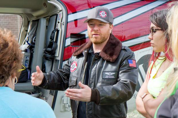 Flight paramedic Reed Lawson explains the benefits of being on a membership plan with Classic Air Medical during a health fair at Coal Ridge High School.