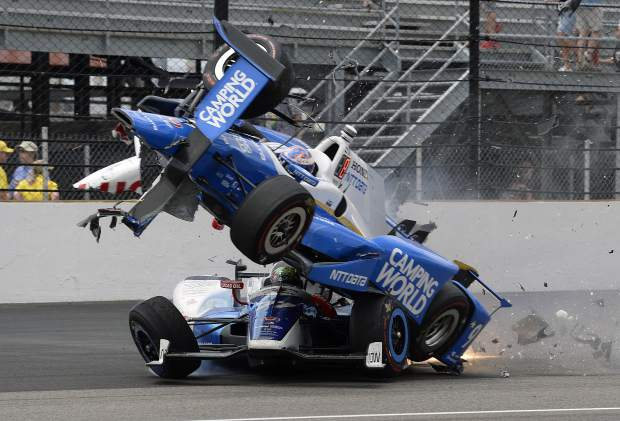 The car driven by Scott Dixon, of New Zealand, goes over the top of Jay Howard, of England, in the first turn during the running of the Indianapolis 500 auto race at Indianapolis Motor Speedway, Sunday, May 28, 2017, in Indianapolis. (AP Photo/Marty Seppala)