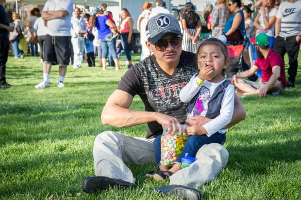 Hector Cruz and his three-year-old daughter Lexi eat popcorn and listen to live music in Sopris Park at the Festival Las Americas on Friday evening.