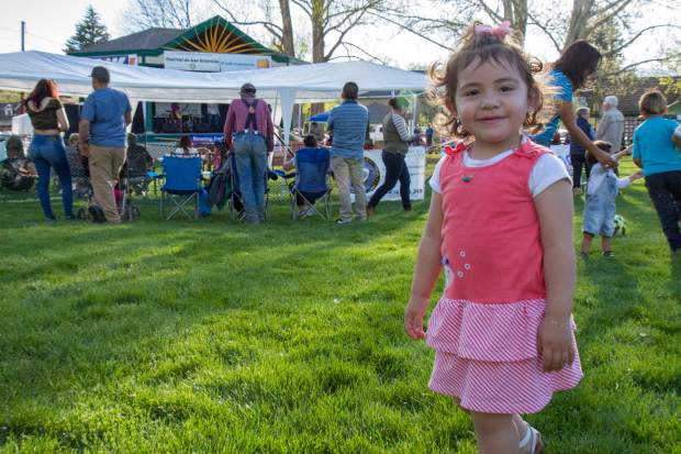 Two-year-old Lindsay Soltero plays in the grass at the Festival Las Americas on Friday evening.