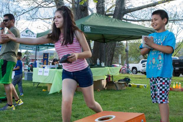 Jasiel Martinez, 9, and Citlali Torrez, 13, play cornhole at the Festival Las Americas in Sopris Park on Friday evening.