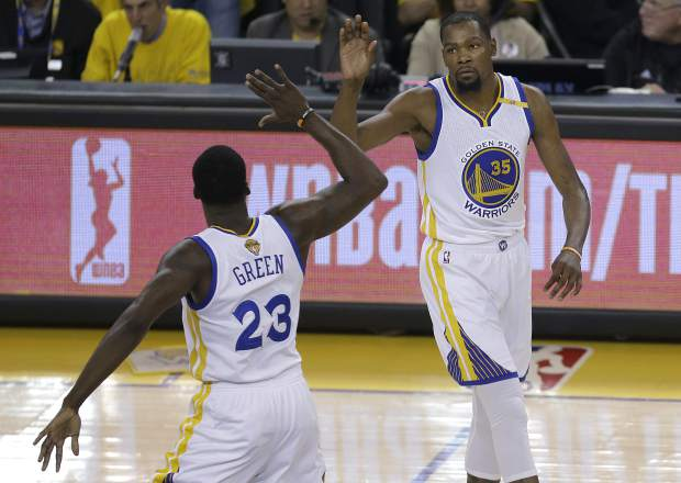 Golden State Warriors forward Kevin Durant (35) and forward Draymond Green (23) celebrate during the first half of Game 2 of basketball's NBA Finals against the Cleveland Cavaliers in Oakland, Calif., Sunday, June 4, 2017. (AP Photo/Ben Margot)
