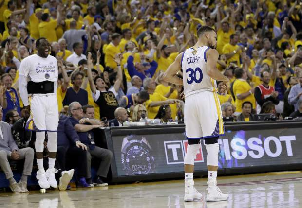 Golden State Warriors forward Draymond Green, left, and fans cheer after guard Stephen Curry (30) scored against the Cleveland Cavaliers during the second half of Game 2 of basketball's NBA Finals in Oakland, Calif., Sunday, June 4, 2017. (AP Photo/Marcio Jose Sanchez)