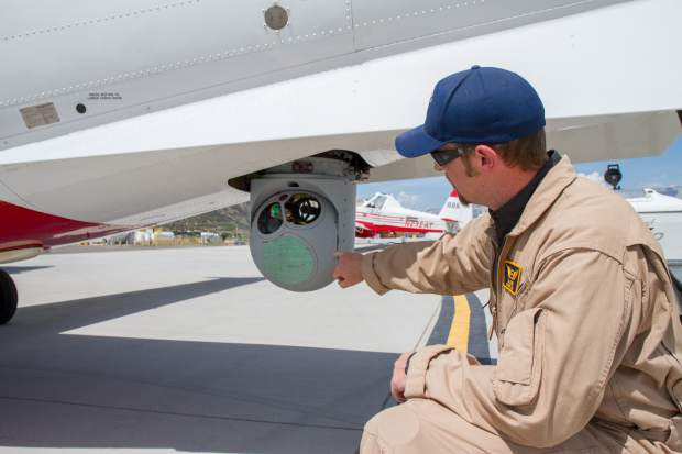 DJ Chess with the Division of Fire Prevention and Control demonstrates how the MX 15 Infared-2 color sensor camera works. The camera can be used to locate burning or hot objects from thousands of feet in the air.