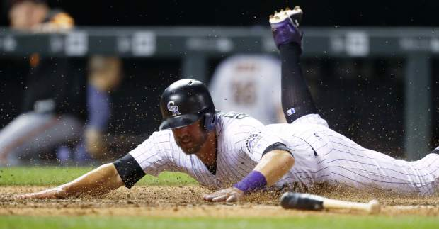 Colorado Rockies' Mark Reynolds slides across home plate to score the winning run on a single by Raimel Tapia off San Francisco Giants relief pitcher Hunter Strickland during the ninth inning of a baseball game Thursday, June 15, 2017, in Denver. The Rockies won 10-9. (AP Photo/David Zalubowski)