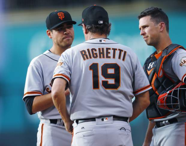 San Francisco Giants pitching coach Dave Righetti, front, confers with starting pitcher Matt Moore, back left, as catcher Buster Posey listens after Moore gave up an RBI single to Colorado Rockies' Mark Reynolds during the first inning of a baseball game Thursday, June 15, 2017, in Denver. (AP Photo/David Zalubowski)