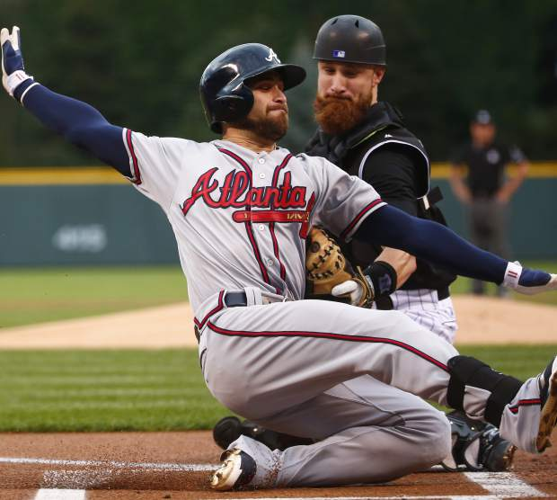 Atlanta Braves' Ender Inciarte, left, is tagged out at home plate by Colorado Rockies catcher Jonathan Lucroy, right, during the first inning of a baseball game Monday, Aug. 14, 2017, in Denver. (Ap Photo/Jack Dempsey)