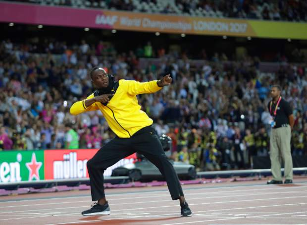 Jamaica's Usain Bolt makes his trademark gesture during a lap of honor at the end of the World Athletics Championships in London Sunday, Aug. 13, 2017. (AP Photo/Matt Dunham)