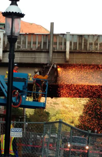 A worker cuts away metal from the Grand Avenue bridge structure that's being demolished.