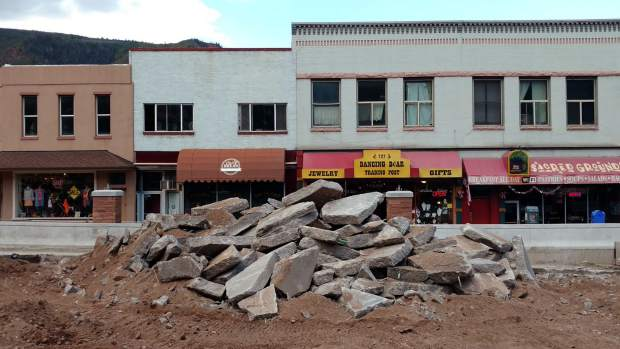 Chunks of the old Grand Avenue bridge deck await loading as workers took a lunch break Monday in downtown Glenwood Springs.