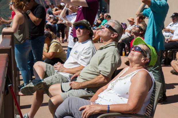 Hundreds of people use their special eclipse glasses provided by the Glenwood Caverns Adventure park during the peak time of the Great American Eclipse monday morning.
