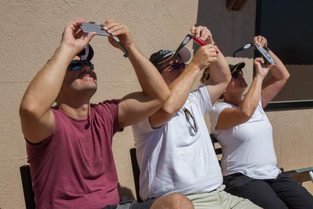 People try to take photos of the eclipse with their special eclipse glasses at the Adventure Park.