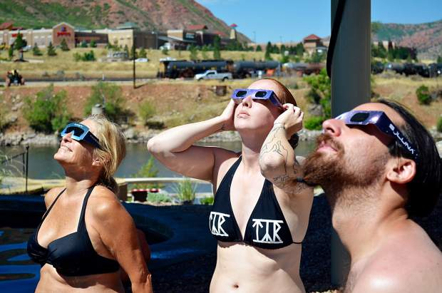 Kathy Stahlman, left, Jennifer Lostly and Brian Glaser view the solar eclipse from Iron Mountain Hot Springs Monday morning. Stahlman was reliving an experience she had as a 5-year-old, while the other two were in town for Lostly's birthday.