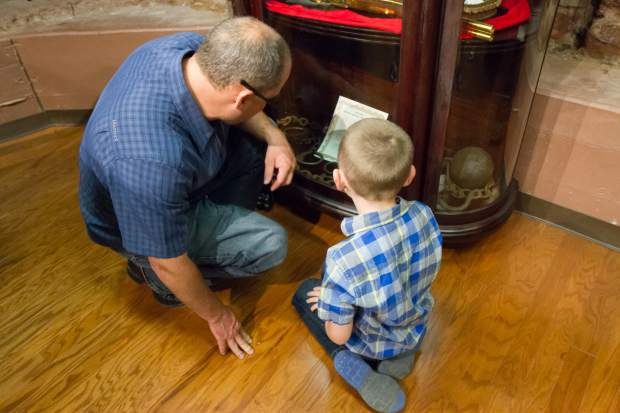 Jared and seven-year-old Ryder Kochevar look at a case holding articfacts at the grand opening of the Doc Holliday Museum on Friday evening.