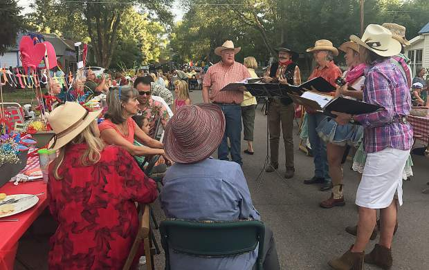 A group of western troubadours serenade a table of diners during Our Town, One Table in Carbondale. The Sunday potluck dinner was the third annual event.