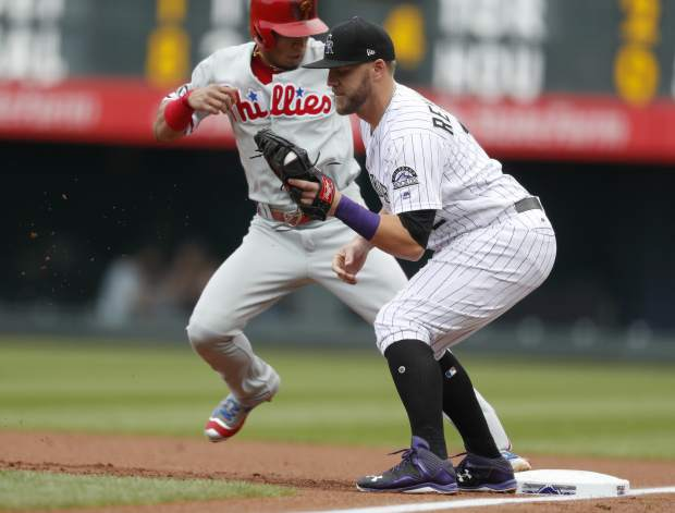 Colorado Rockies first baseman Mark Reynolds, front, fields the pickoff throw as Philadelphia Phillies' Cesar Hernandez returns to first base in the first inning of a baseball game, Sunday, in Denver.