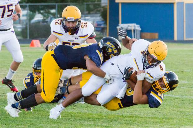 A host of Rifle Bears defenders wrestle Basalt running back Noah Williams to the ground during Rifle's 34-14 win over the Longhorns.