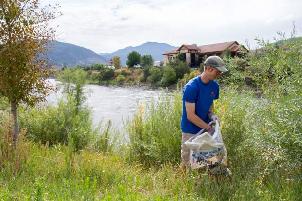 A volunteer checks the riverbank for trash near the Whitewater Park Saturday morning.