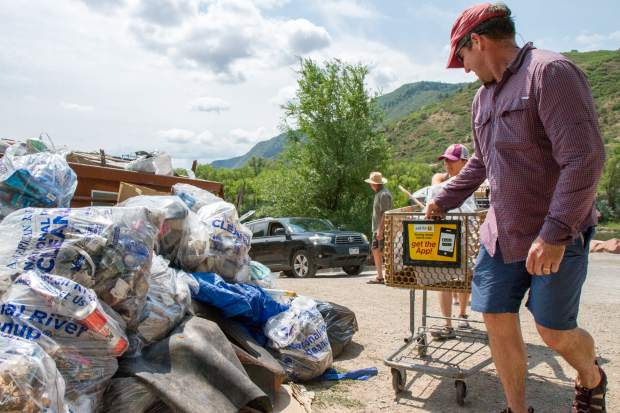 Andy Mueller drops off a shopping cart full of trash that was found near the Roaring Fork river behind Safeway.