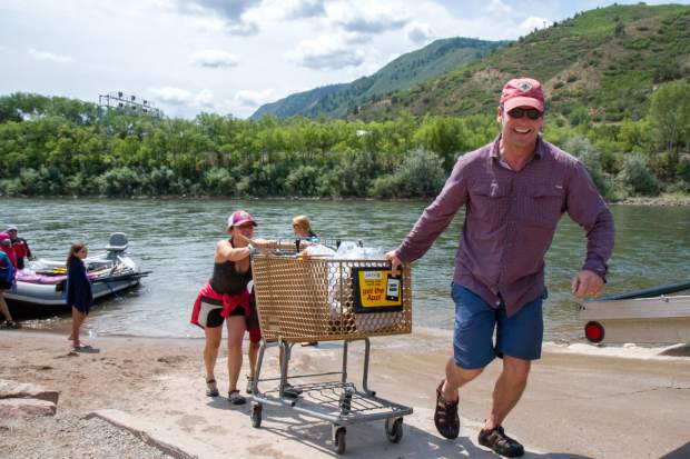 Andy Mueller and Anna Itenberg push a shopping cart full of trash up the boat ramp at Two Rivers Park. The shopping cart and trash was found along the Roaring Fork River behind Safeway.