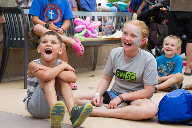 Six-year-old Kalum Troxel and Maisie Smith, 12, have fun watching the Salida Circus performers at the summer block party in downtown Glenwood Saturday evening.