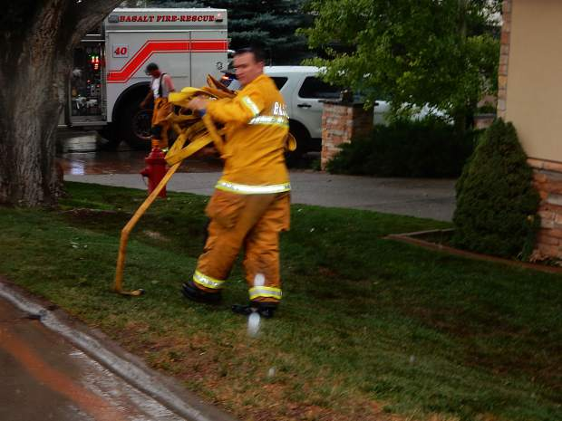 Basalt Deputy Fire Chief Pete Bradshaw rolls up hose used to drain the water out of a home in Elk Run subdivision Friday afternoon.