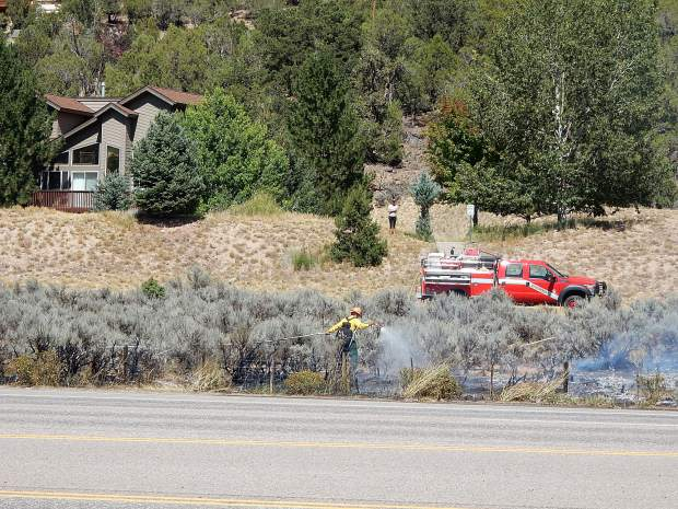 A homeowner looks on in the background while a Basalt firefighter mops up hotspots Friday.