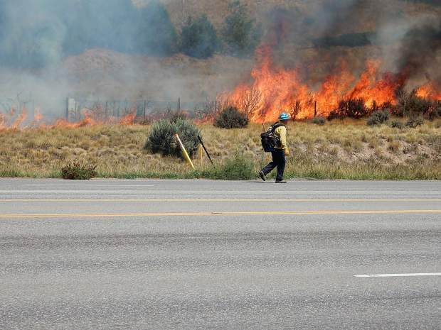 A Basalt firefighter moves into position while flames are crackling Friday.