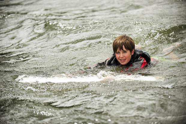 Spencer Perley, 14, gets on top of his sunfish sailboat after purposefully capsizing on Tuesday on Ruedi Reservoir.