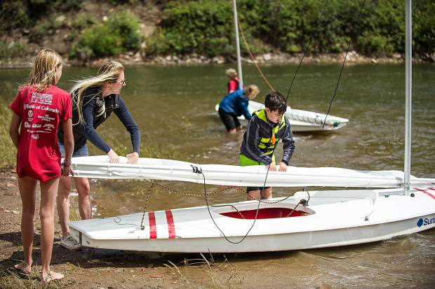 Courtney Sheeley Wyckoff helps Hope White, 12, and Noah Incze, 10, properly roll up a sail on Tuesday at the Aspen Yacht Club.