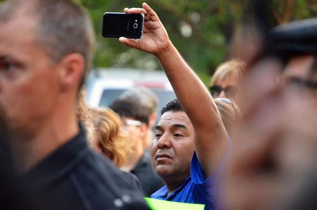 Around 100 people crowded into a protest rally Tuesday morning to listen to several young people, all recipients of Deferred Action for Childhood Arrivals, tell their stories.