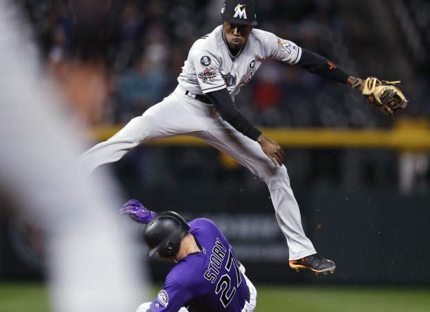 Miami Marlins second baseman Dee Gordon, top, jumps over Colorado Rockies' Trevor Story after forcing him out at second base on the front end of a double play hit into by Jonathan Lucroy during the fifth inning of a baseball game Monday, Sept. 25, 2017, in Denver. Miami won 5-4. (AP Photo/David Zalubowski)