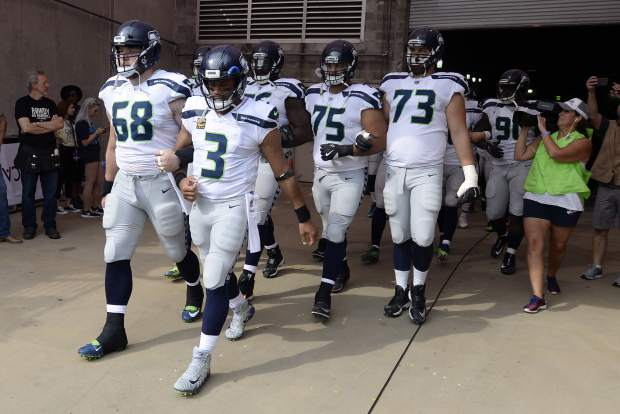 Seattle Seahawks quarterback Russell Wilson (3) and center Justin Britt (68) walk to the field with arms linked after the national anthem had been played before an NFL football game between the Seahawks and the Tennessee Titans Sunday, Sept. 24, 2017, in Nashville, Tenn. Neither team was present on the field for the playing of the anthem. (AP Photo/Mark Zaleski)