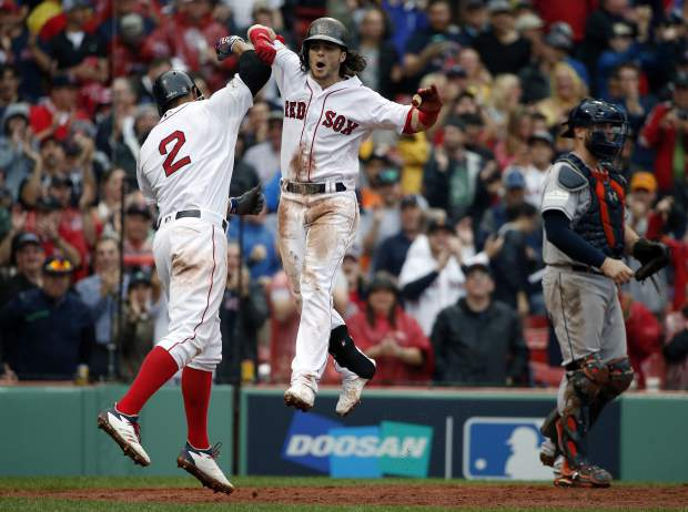 Boston Red Sox's Andrew Benintendi, center, celebrates his two-run home run with Xander Bogaerts, left, during the fifth inning in Game 4 of baseball's American League Division Series against the Houston Astros, Monday, Oct. 9, 2017, in Boston. At right is Astros catcher Brian McCann.(AP Photo/Michael Dwyer)