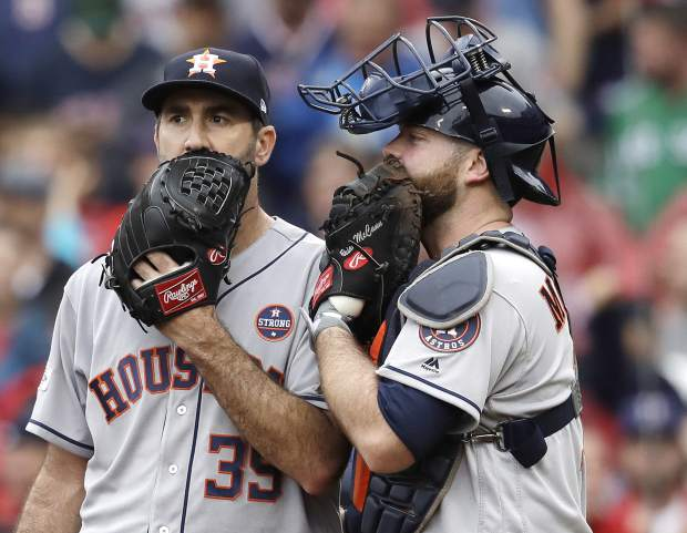 Houston Astros relief pitcher Justin Verlander, left, and catcher Brian McCann talk during the fifth inning of Game 4 of baseball's American League Division Series against the Boston Red Sox, Monday, Oct. 9, 2017, in Boston. (AP Photo/Charles Krupa)