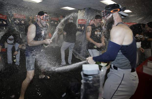 Houston Astros players celebrate in the clubhouse after eliminating the Boston Red Sox with a 5-4 victory in Game 4 of baseball's American League Division Series, Monday, Oct. 9, 2017, in Boston. (AP Photo/Charles Krupa)