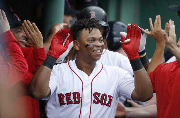 Boston Red Sox's Rafael Devers, center, is congratulated by teammates in the dugout after his two-run home run against the Houston Astros during the third inning in Game 3 of baseball's American League Division Series, Sunday, Oct. 8, 2017, in Boston. (AP Photo/Michael Dwyer)