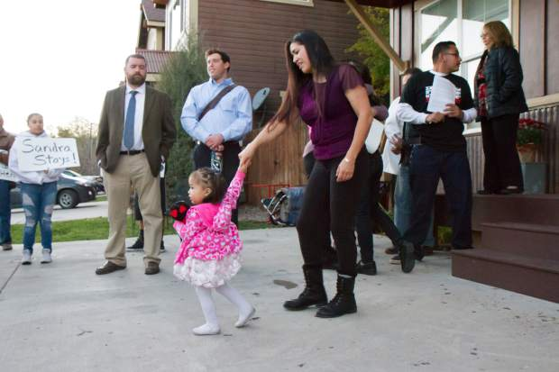 Sandra Lopez and her 2-year-old daughter Areli walk outside of the Parsonage in which Sandra will be taking sanctuary in Carbondale.