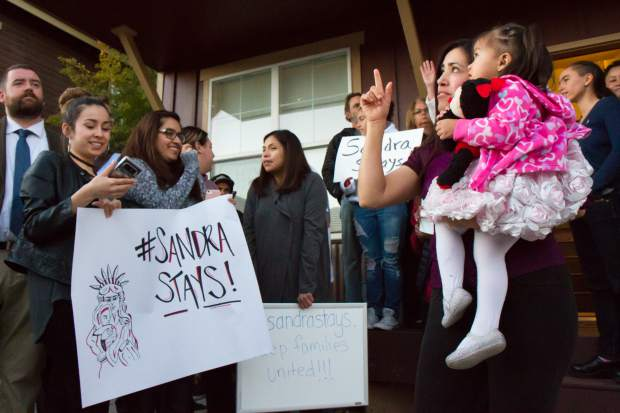 Sandra Lopez and her 2-year-old daughter Areli stand with her supporters during the press conference in Carbondale on Tuesday evening.