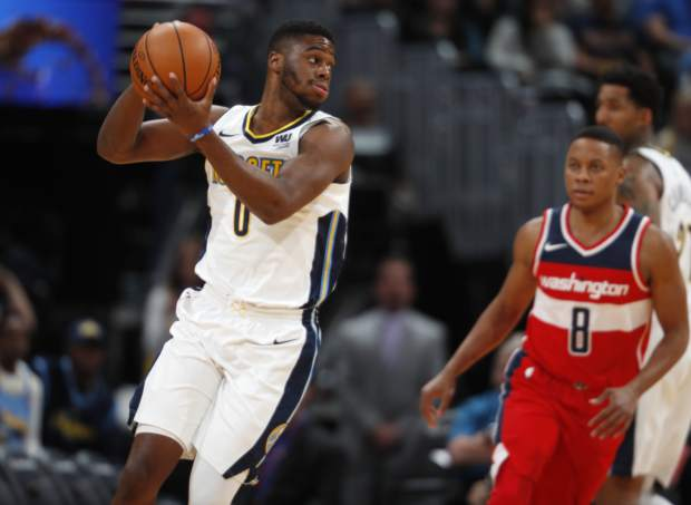 Denver Nuggets guard Emmanuel Mudiay, left, pulls in a loose ball in front of Washington Wizards guard Tim Frazier in the first half of an NBA basketball game, Monday, Oct. 23, 2017, in Denver. (AP Photo/David Zalubowski)