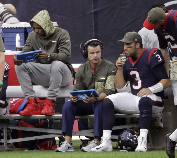 Injured Houston Texans quarterback Deshaun Watson, front left, sits on the bench with quarterback Tom Savage (3) during the first half of an NFL football game against the Indianapolis Colts, Sunday, Nov. 5, 2017, in Houston. (AP Photo/David J. Phillip)